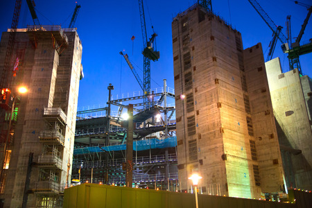 famous industries: LONDON, UK - DECEMBER 19, 2014: Building site with cranes in the City of London business. New development next to bank of England. Night view