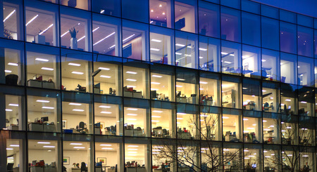 modern life: LONDON, UK - DECEMBER 19, 2014: Office block with lots of lit up windows and late office workers inside. City of London business aria in dusk.
