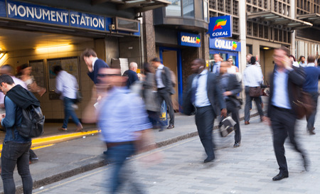 LONDON, UK - APRIL15, 2015: City of London, tube commuters walking in front of Londons tube station. Business people blur.
