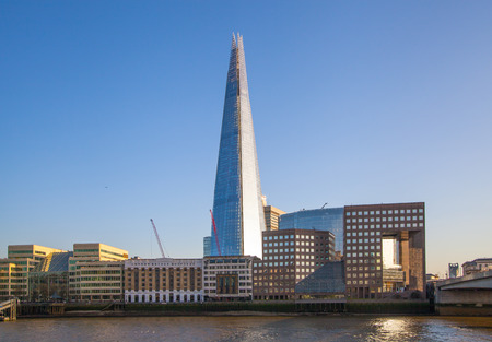 shard: LONDON, UK - APRIL15, 2015: Shard of glass in sunset. Panoramic view of south bank river Thames walk.