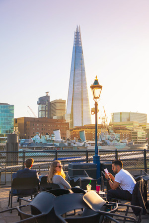 shard of glass: LONDON, UK - APRIL15, 2015: Little cafe and tourists in front of Shard of glass, the tallest building in Europe. South bank of river Thames walk.