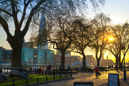 royal park: LONDON, UK - APRIL15, 2015: Tower park in sun set. River Thames side walk with people resting by the water