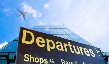 Departure sign and airplane in the blue sky photo