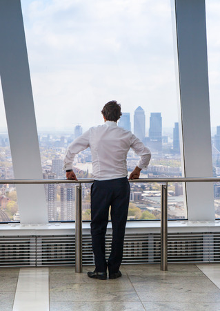 looking through window: LONDON UK  APRIL 22 2015: Businessman looking at London through the window of WalkieTalkie building. View includes Canary Wharf business and banking aria. Business concept image
