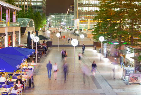 caffee: LONDON UK  JULY 29 2014: Canary Wharf square view in night lights with office workers chilling out after working day