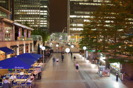 chilling out: LONDON UK  JULY 29 2014: Canary Wharf square view in night lights with office workers chilling out after working day