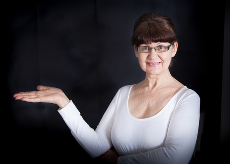 good looking woman: Mature good looking woman with open hand holding something blank