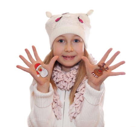 Happy girl demonstrating painted Christmas symbols on her hands. photo