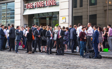 socialising: LONDON, UK - APRIL15, 2015: Exterior of pub in the City of London with lots of people drinking and socialising after work. Editorial