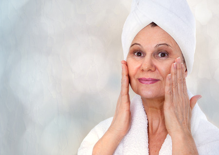 eye cream: Spa concept. Aged good looking woman with white towel on her head