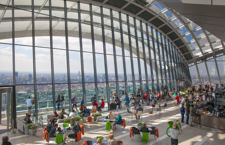 city building: LONDON, UK - APRIL 22, 2015: People in the restaurant of the Sky Garden Walkie-Talkie building. Viewing platform is highest UK garden, locates at the 32 floor and offers amazing skyline of London city.