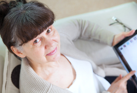 good looking woman: Pension age good looking woman searching in internet on tablet device