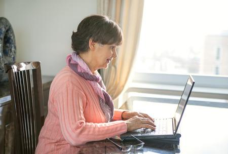 Elderly good looking woman working on laptop. Portrait in domestic interior