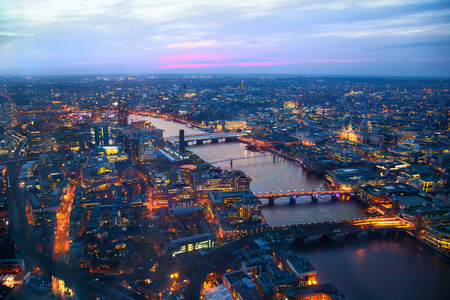 aerial: LONDON, UK - APRIL 15, 2015: City of London panorama in sunset and first night lights. Editorial