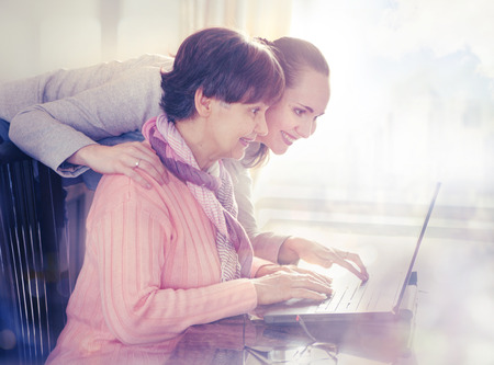 social care: Younger woman helping an elderly person using laptop computer for internet search. Young and pension age generations working together.