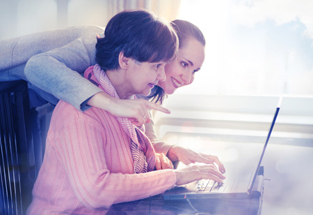 help: Younger woman helping an elderly person using laptop computer for internet search. Young and pension age generations working together.