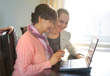 Younger woman helping an elderly person using laptop computer for internet search. Young and pension age generations working together.