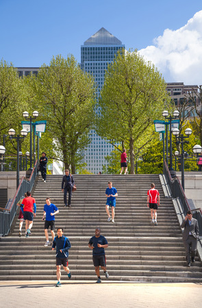 green building: LONDON, UK - May 21, 2015: Canary Wharf banking aria. Stairs up to the square with running people. Business people running during lunch break Editorial