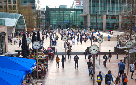 LONDON, CANARY WHARF UK - MARCH 2, 2015: Modern architecture of Canary Wharf business aria with lots of walking people and clock on the main square