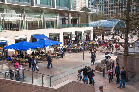greater: LONDON, CANARY WHARF UK - MARCH 2, 2015: Modern architecture of Canary Wharf business aria with lots of walking people and clock on the main square