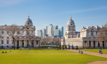classic contrast: LONDON, UK - APRIL 14, 2015: Canary Wharf and Greenwich Royal naval chapel and painted hall. Contrast of modern skyscrapers and classic architecture Editorial