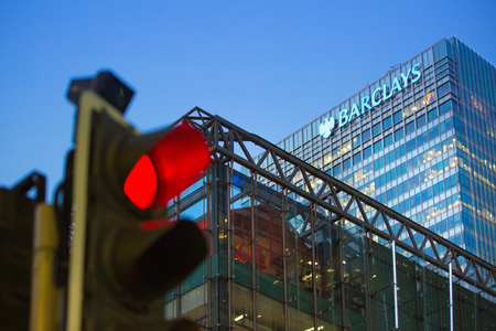 traffic building: LONDON, UK - 7 SEPTEMBER, 2015: Canary Wharf traffic lights showing red and Barclays bank building on the background Editorial