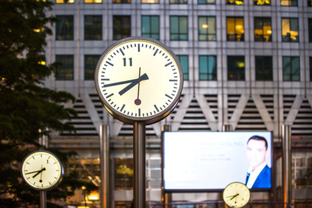 business life: LONDON, UK - 7 SEPTEMBER, 2015: Canary Wharf business life. Clock on the main square showing quarter to eight evening time