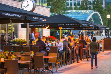 entrance: LONDON, UK - 7 SEPTEMBER, 2015: Canary Wharf night life. People sitting in local restaurant after long hours working day