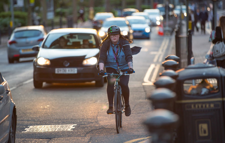 bicycle girl: LONDON, UK - 7 SEPTEMBER, 2015: Londoners commuting from work by bike. Road view with cars and bikers