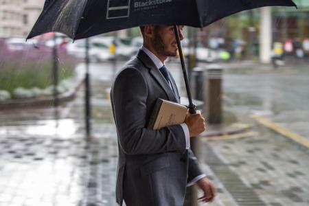 LONDON, UK - SEPTEMBER 17, 2015: Businessman with umbrella  walking in rain. City of London
