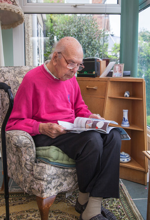 home care: 95 years old English man sitting in chair in domestic environment. Health and care concept