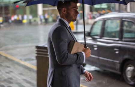 rain wet: LONDON, UK - SEPTEMBER 17, 2015: Businessman with umbrella  walking in rain. City of London