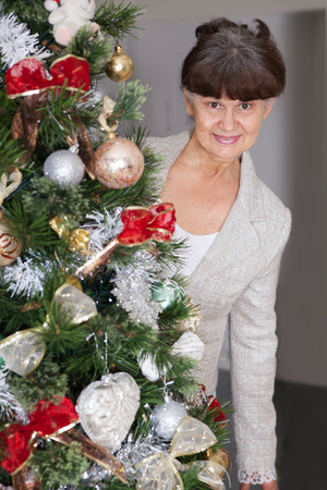 woman portrait: Mature age good looking woman against of Christmas tree. Christmas background