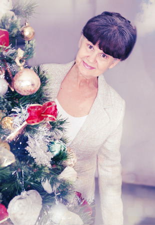 good looking woman: Mature age good looking woman against of Christmas tree. Christmas background