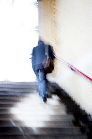 career man: Businessmenwalking up to stairs, blur background. London