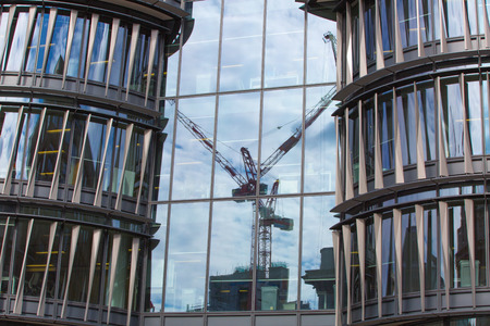 office buildings: LONDON, UK - SEPTEMBER 17, 2015:  Office block windows with cranes reflection. Business background Editorial