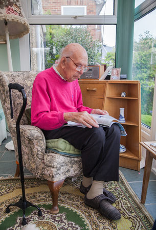 health care: 95 years old English man sitting in chair in domestic environment. Health and care concept