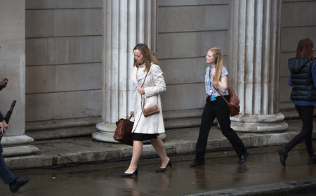 woman business suit: LONDON, UK - SEPTEMBER 17, 2015: Businesswoman walking on the street against of Bank of England wall