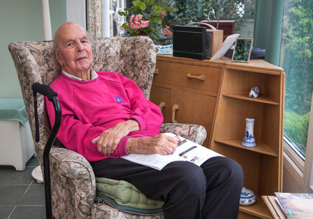 eldercare: 95 years old English man sitting in chair in domestic environment. Health and care concept