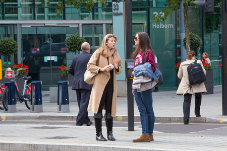 british people: LONDON, UK - SEPTEMBER 19, 2015: Two young woman talking in Holborn street Editorial