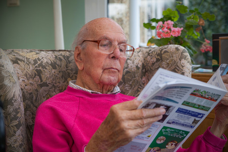 APARTMENT LIVING: 95 years old English man sitting in chair in domestic environment. Health and care concept