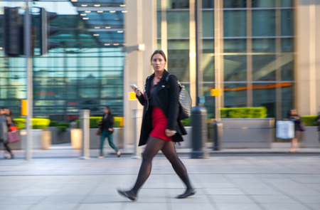 woman shop: LONDON, UK - MAY 21, 2015:  Blur of Business people walking on street after working day. Canary Wharf