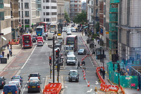 road traffic: LONDON, UK - SEPTEMBER 19, 2015: Holborn street with traffic and people crossing the road