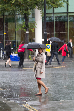 rain wet: LONDON, UK - SEPTEMBER 17, 2015: Woman with umbrella  walking in rain. City of London