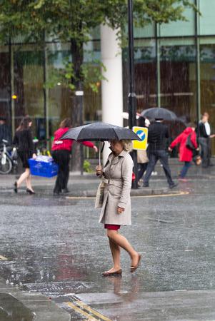 LONDON, UK - SEPTEMBER 17, 2015: Woman with umbrella  walking in rain. City of London