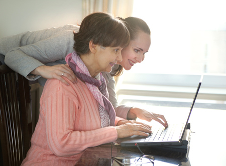 eldercare: Younger woman helping an elderly person using laptop computer for internet search. Young and pension age generations working together.