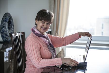 good looking woman: Elderly good looking woman working on laptop. Portrait in domestic interior