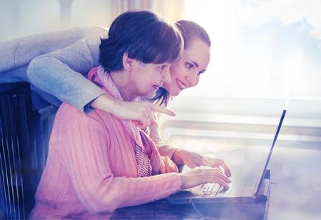 personen: Jongere vrouw helpen van een oudere persoon met behulp van laptop computer voor internet zoeken. Jong en pensioenleeftijd generaties samenwerken.