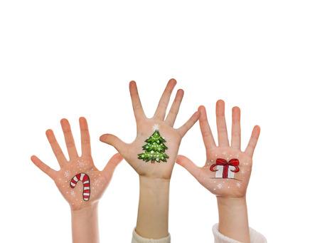 kids painted hands: Christmas symbols painted on kids hands. Santa, snowman, Christmas tree, present box, reindeer etc
