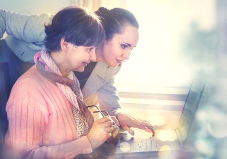 インターネット検索用のラップトップ コンピューターを使用して高齢者を助ける若い女性。若くて年金年齢世代がともに働きます。 写真素材